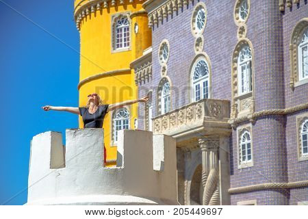 Blonde carefree woman with open arms on tower of colorful Pena National Palace, Unesco Heritage and one of Seven Wonders of Portugal. Happy female tourist in the most visited attraction of Sintra.