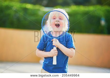 Little Boy Playing Badminton On The Playground