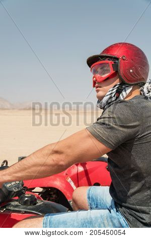 Young Guy During Desert Excursion By Quad - Man In Helmet And Adventure Clothes In Exotic Scenarios