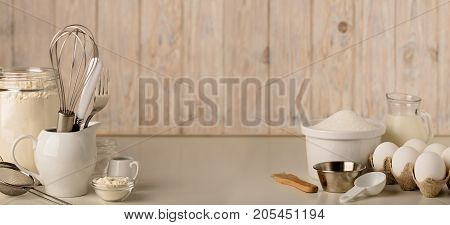 Kitchen utensils and tools for homemade baking on a light wooden background. Selective focus.