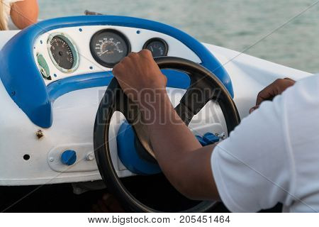 Men's hands on the steering wheel of a motor boat.