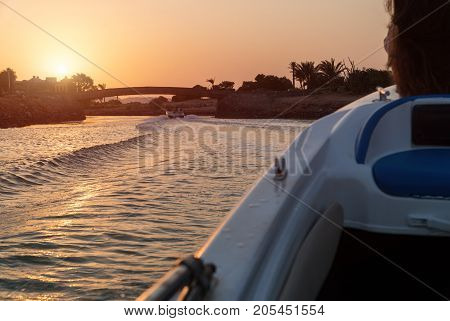 The boat swims into the sunset. Sunset in the city of El Gouna. Waves on the water.