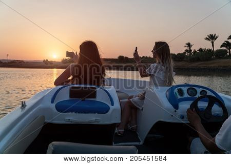 Girls ride a boat on the channels of the city of El Gouna and make photo on a mobile phone.