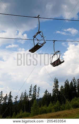 Mountain chair ski lift at blue sky, white clouds