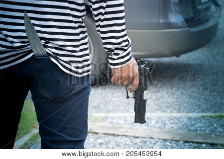 Closeup robber holding a gun walking to the car for rob