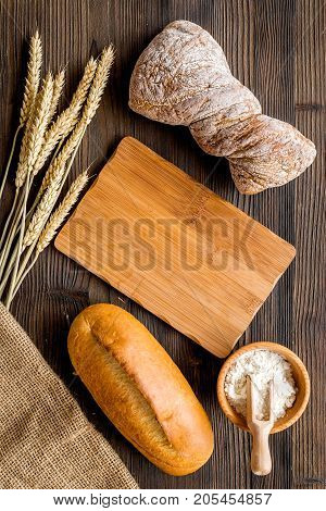 baking fresh wheaten bread on bakery work table wooden background top view space for text