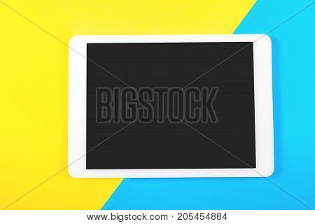 Digital tablet computer on blue and yellow background. Top view