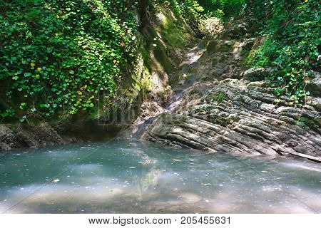 Small beautiful mountain lake with stagnant water and a creek flowing into it among the jungle