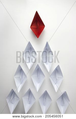 Red paper ship leading white ones leadership concept