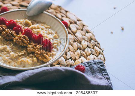 Morning breakfast oatmeal in milk with raspberries and walnuts