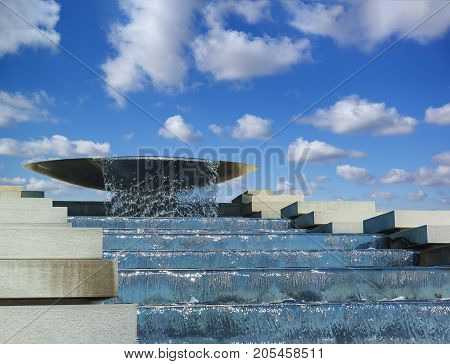 Water flows from bowl cascading fountain. An artificial waterfall on the background of blue sky