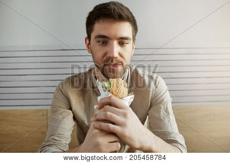 Attractive dark haired guy sitting in cafe, looking with happy expression at sandwich, being happy to eat something after all day at work. Hungry man going to eat burger