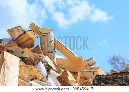 Chopped Firewood Against The Blue Sky. Copy Space For Text