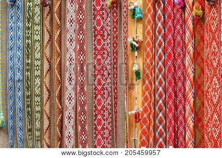 Collection of different patterns of national belarusian hand-plaited sashes. Linen belt with ornaments that hang in a row.