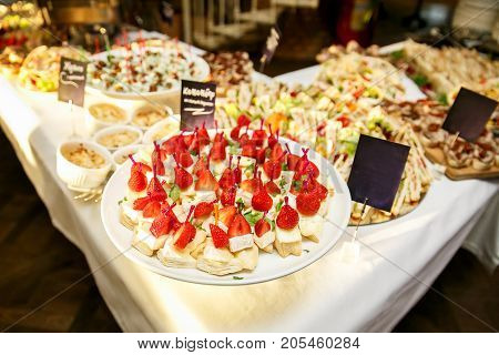 Event catering. Many dishes with cheese, meat, strawberries.