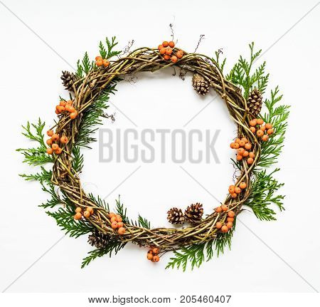 Festive wreath of grape vines with thuja branches rowanberries and cones. Christmas DIY wreath. New Year round wreath on white background. Flat lay top view