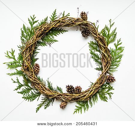 Festive wreath of grape vines with thuja branches and cones. Natural DIY wreath. Christmas or any other holiday decorative wreath on white background. Flat lay top view