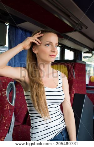 A young woman sitting comfortably on the bus.