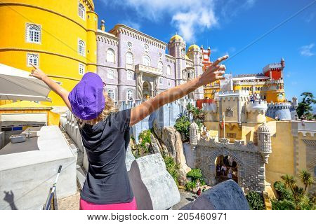 Aerial view of happy caucasian woman with open arms loooking Pena Palace. Pena Castle is Unesco Heritage and one of Seven Wonders of Portugal.Female tourist enjoys of most visited attraction of Sintra