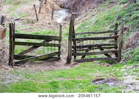 An Closed Gate In A Wooden Fence On A Village Road.