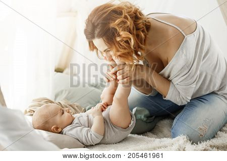 Happy mother playing with newborn baby spending best maternity moments in cozy bedroom. Warm family atmosphere. Family concept