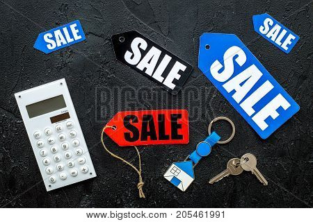 Count the benefits from the sale. Word sale on colored labels near calculator on black background top view.