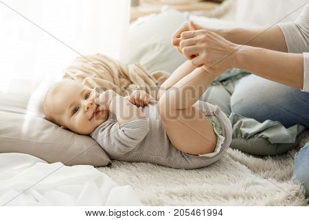 Close up portrait of little newborn son looking at camera while playing with mother. Kid smiling and put his fingers in mouth lookin happy and carefree