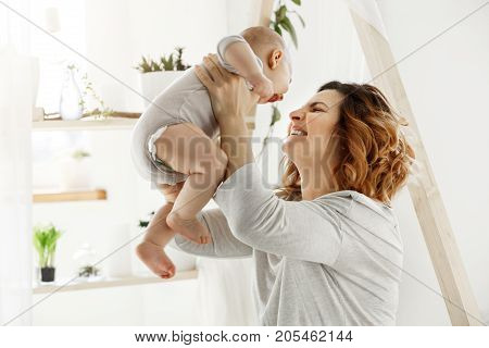 Happy smiling mother playing with newborn child in comfy light bedroom in front of window. Moments of motherhood happiness with kids. Family concept