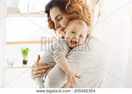 Happy young mom holds precious little child and gently hugging his little body. Kid laughing joyfully and looking in camera with big grey eyes