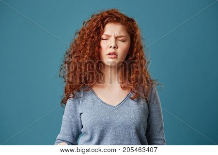 Close up of pretty young girl with wavy ginger hair and freckles in grey shirt having headache after sleepless night