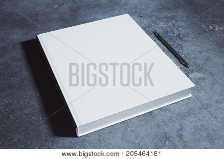 Blank white hardcover diary and pen placed on concrete desk. Supplies stationery items paperwork concept. Mock up 3D Rendering