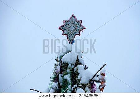New year or Christmas background.Christmas star on a Christmas tree.Decorated Christmas tree standing in the street in the snow. Christmas decorations tinsel. Snowflakes. Garland