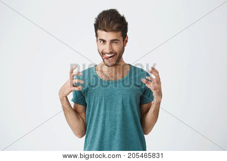 Studio portrait of funny expressive spanish guy in blue t-shirt, playing fool showing tongue and teeth, having fun indoors. Human face expressions