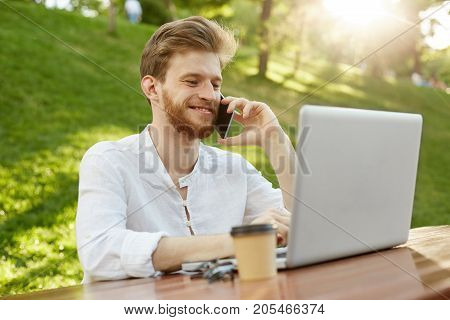 Young beautiful redhead male freelancer with good haircut and beard, working on laptop in park, talking on phone with boss and feeling happy about job achievements.