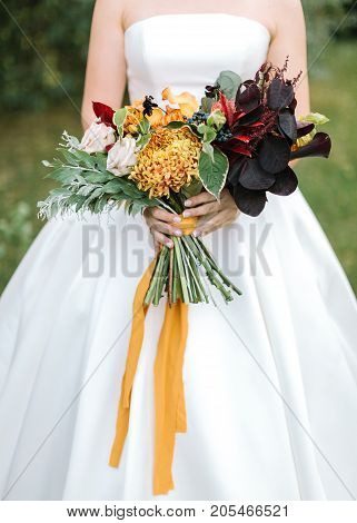 style, floral arranging, wedding concept. young woman dressed in extremely beautiful snowy white dress with puffy skirt is holding great bunch of different flowers stretched with yellow ribbons