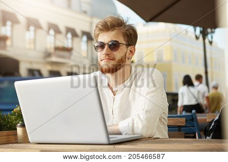 Young mature red-haired bearded guy in stylish clothes and tan glasses sitting outside in sunny summer day, working on team project via laptop and feeling happy