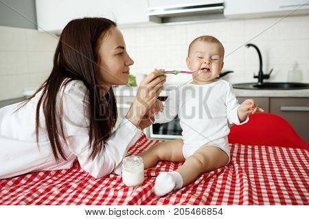 Smiling young mother trying to feed her little lovely son with spoon while he turning head side, refusing to eat with disgust expression