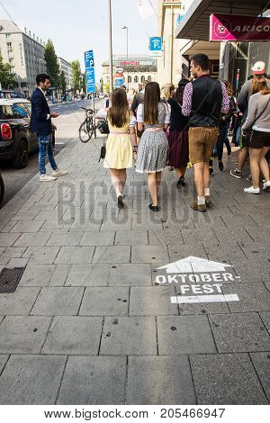 MunichGermany-September 242017: Visitors to the Oktoberfest walk past a sign painted on the sidewalk indicating the way.