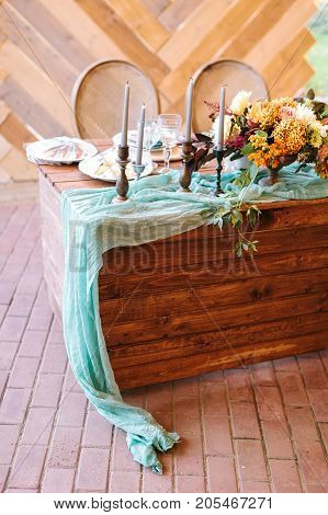 table setting, catering, wedding decoration concept. there are lots of candles in high holders, marvelous bunch of flowers and prepared treatment for guests on wooden table with turquoise draping
