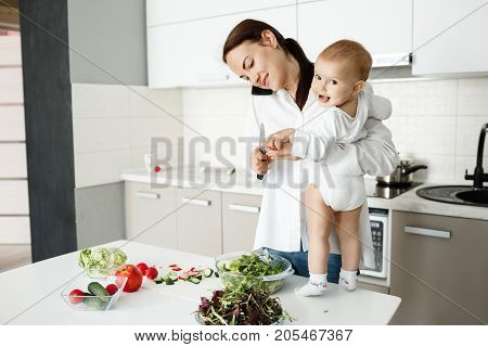 Handsome dark haired mother cooks salad for breakfast and talking on phone while little cute son standing on table near mom and looking in camera