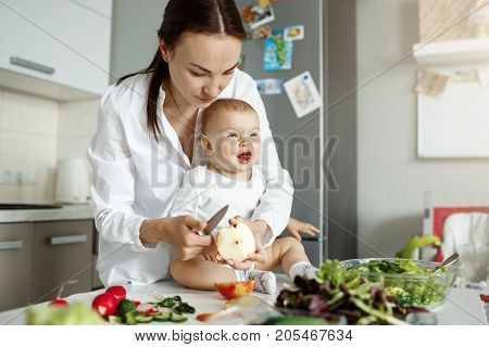 Little newborn baby sitting at table in front of mother with funny expression while mom cooking salad for family lunch. Family concept