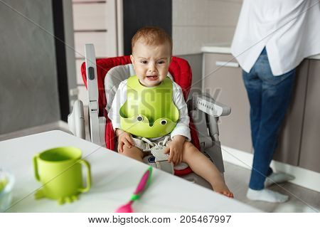 Portrait of little scared baby boy sitting in baby chair in kitchen, crying and screaming while mother cooking him food