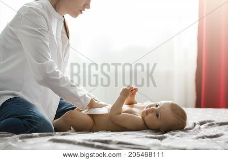 Beautiful young mother in white shirt and jeans putting diaper on cute newborn baby preparing for family dinner with grandparents. Spending special time with family