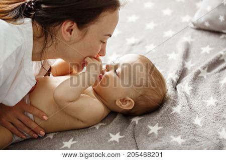 Close up of happy good looking mother playing with her newborn son, kissing and gently biting his little hands. Happy motherhood concept
