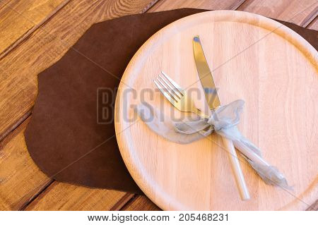 tableware, feast decoration, party concept. on the wooden table there is great plate carved out of wood of light colour and such elegant silverware as fork and knife strapped with lilac ribbon