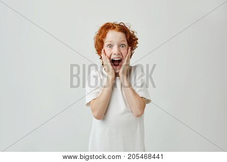 Excited redhead boy with freckles holding face with hands, with happy expression and opened mouth after parents gave him sweets