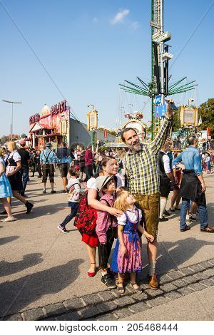 MunichGermany-September 242017: A family in tradtional bavarian clothes takes a selfie with their smartphone at the Oktoberfest grounds