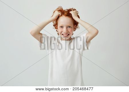 Portrait of beautiful red head child with freckles smiling brightfully with teeth, holding hair in hands and looking in camera