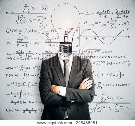 Light bulb headed businessman with folded arms standing on concrete wall background with mathematical formulas. Science concept