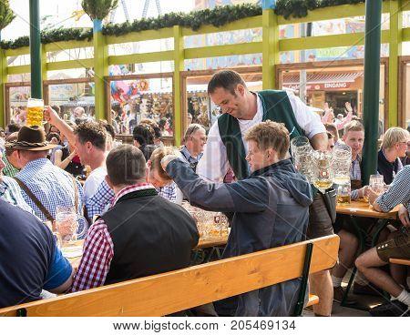 MunichGermany-September 242017A waiter picks up empty beer mugs at a table in a Biergarten at the Oktoberfest